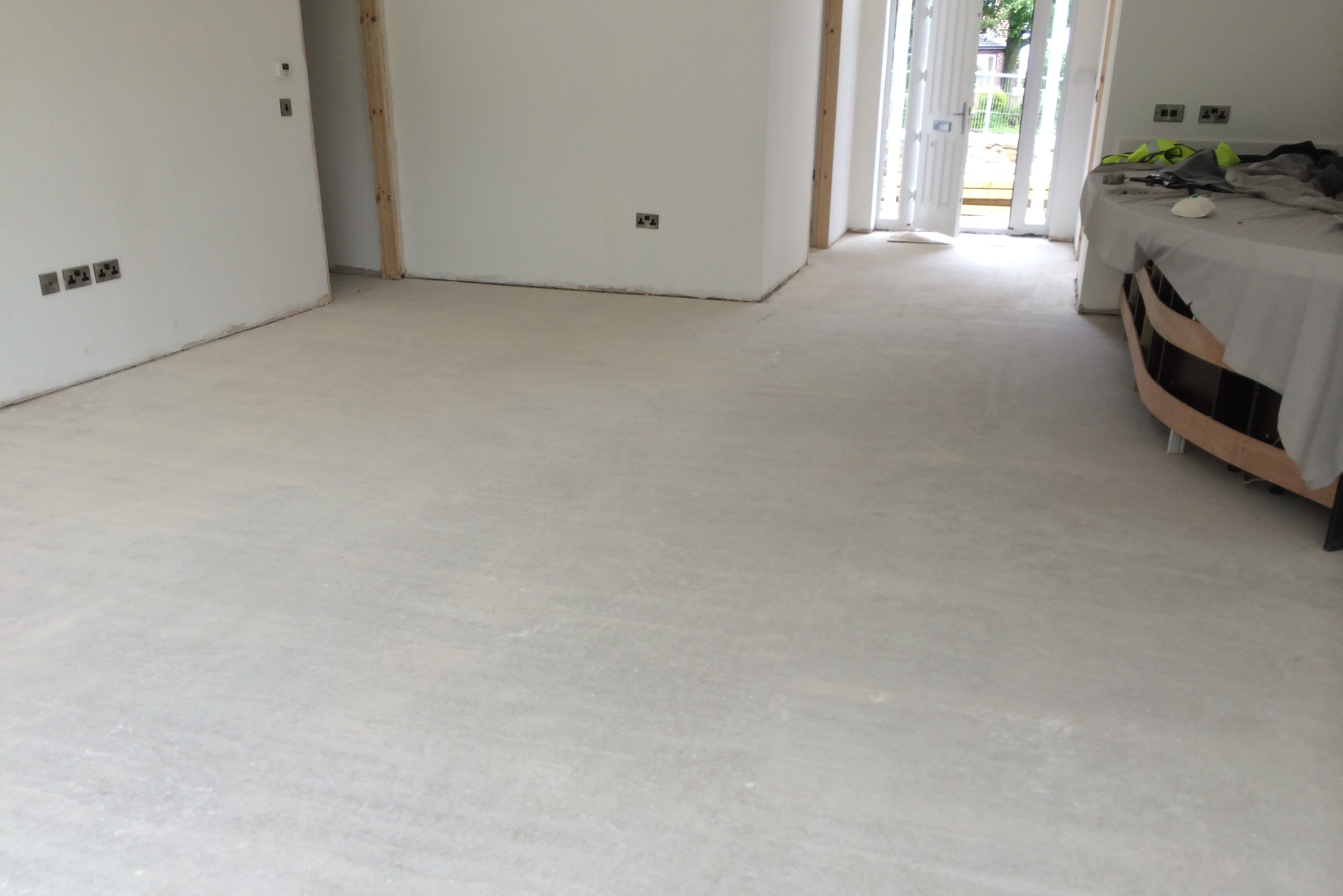 A room after screeding, showing a smooth screeded floor.