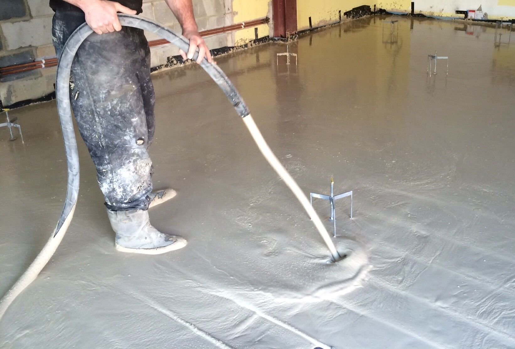 Man pouring liquid screed over underfloor heating system.